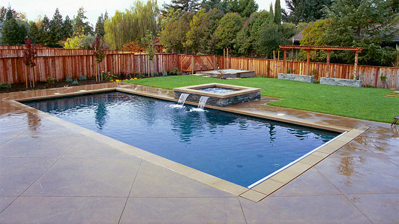 An ordinary backyard becomes a meditative sanctuary, with clean, pure lines and simple shapes. The surfaces are natural stone veneer and scoured concrete, with a simple gray plaster in the pool and spa. The eye is drawn to two shallow spillways - the only movement in a serene landscape.