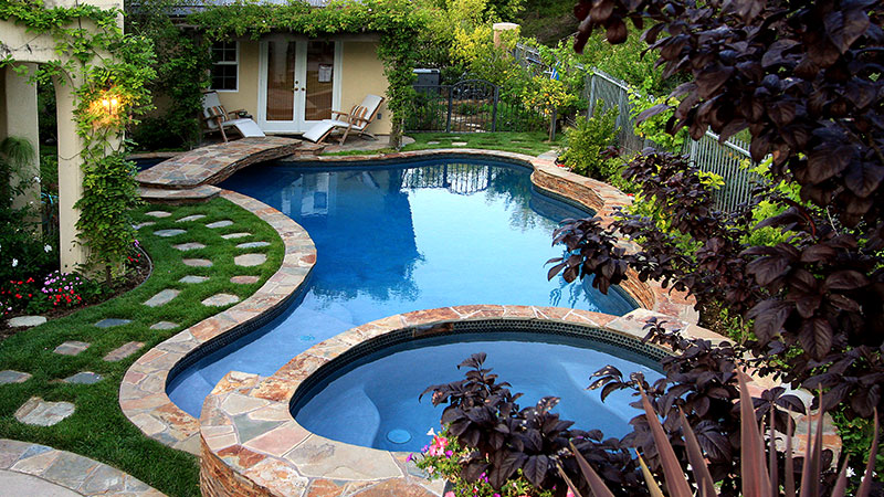 Swan Pools created this custom swimming pool interwined with the custom cottage in the wooded hills of Newport Beach, California.  Custom freestanding swimming pool and raised spa myander between the residence and pool house connected by a stone veneered, raised footbridge spanning the swimming pool and private cove.  Stone coping finishes the swimming pool well including, Caribbean Blue quartz plaster, led lighting, remote systems, and raised spa veneered in stone with custom width coping perfect for cool beachside evening entertaining.