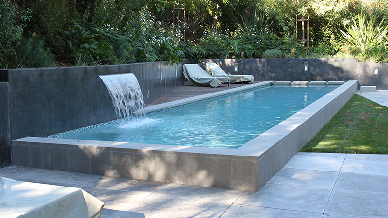 Modern swimming pool construction project in San Jose, California.  Sleek modern design in Silicon Valley with raised composite wood deck, concrete coping, stepping pads, smooth stucco veneered retaining wall and a Jandy/Zodiac sheer descent.  White interior quartz plaster.