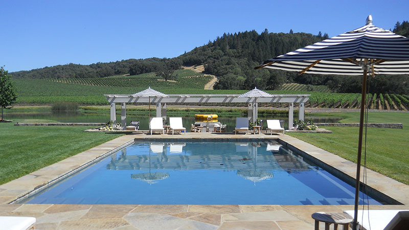 Swan Pools, an award winning swimming pool builder, created a custom sunny oasis in the rolling hills of Northern California.  The classic Californian relaxation swimming pool includes stone coping, stone deck, led lighting, mottled grey plaster, and a freestanding lattice patio cover.  The swimming pool in the surrounding environment invites relaxation on a long, sunny Sunday afternoon.